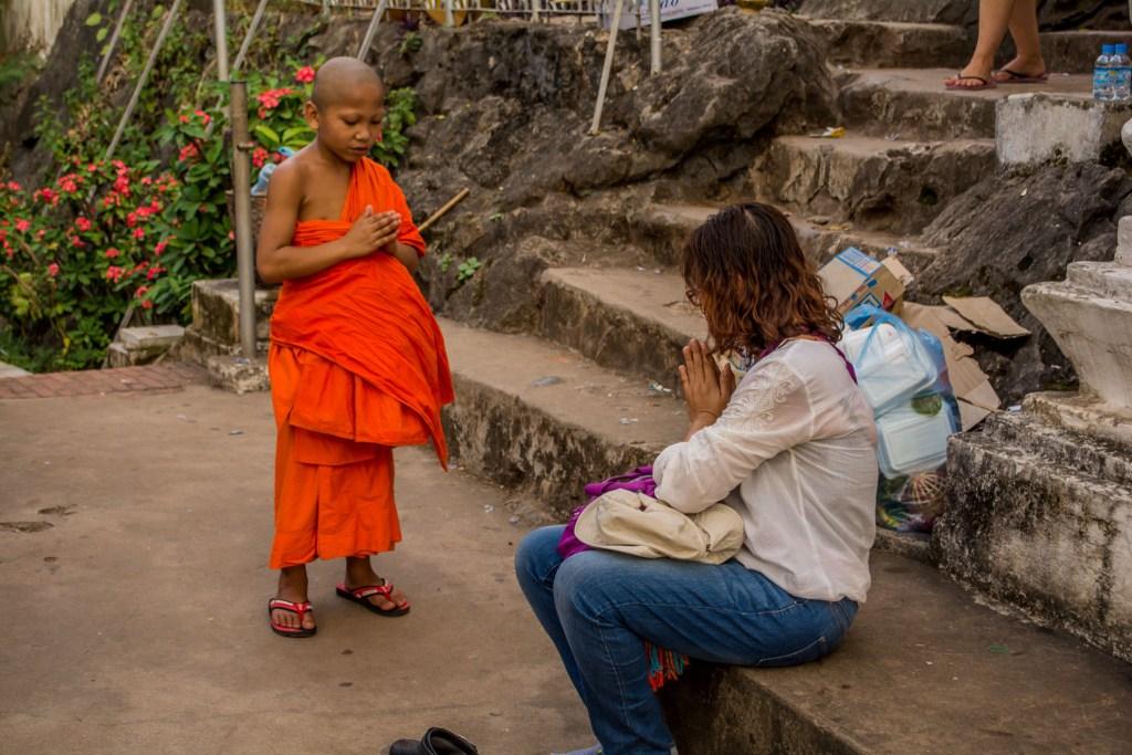 monge cumprimentando turista no laos